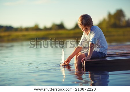 A handsome happy child playing with a tiny boat on water on a sunny summer day. Kids in country. Nature. - stock photo
