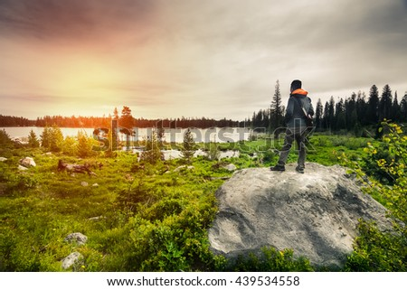 A handsome hiker is standing on the rock looking towards a view of beautiful nature in Grand Teton National Park.  This landscape has rocks, hiker, cloudy sky, and beautiful lake in distance. - stock photo