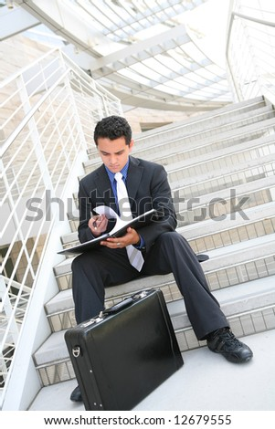 A handsome hispanic business man on the stairs reviewing his notes