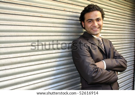 A handsome Indian businessman, posing against a shutter. - stock photo
