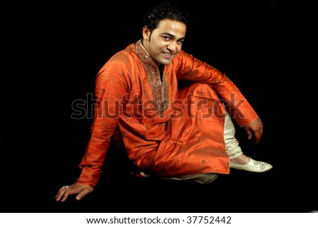 A handsome Indian man in a traditional attire (Shrewani), on black studio background. - stock photo