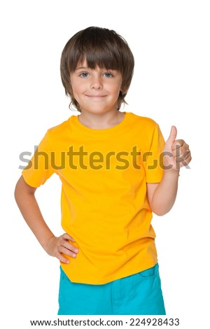 A handsome little boy holds his thumb up on the white background