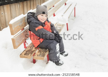 A handsome little boy in winter clothes sitting alone - stock photo