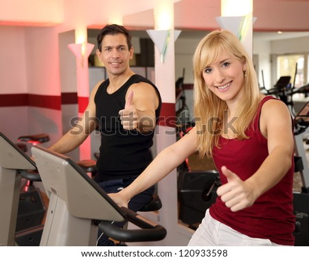 A handsome man and an attractive woman working out on a bicycle in a fitness center