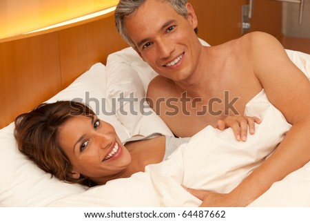 A handsome man and beautiful woman smile while laying happily in bed together