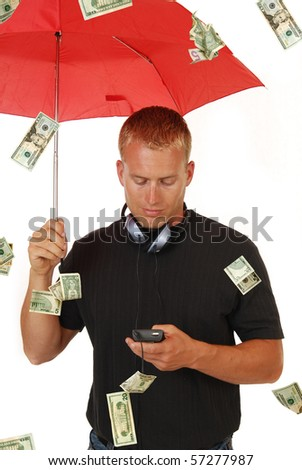A handsome man calmly holds an umbrella in a rain storm of money - stock photo