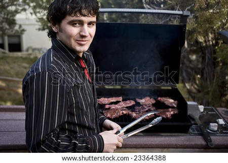 A handsome man grilling steak on the barbeque - stock photo