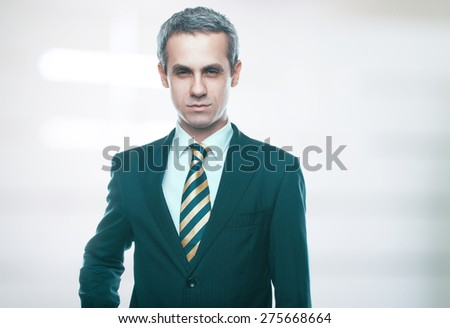 A handsome man in a jacket and tie for business negotiations. Looking at the camera. Office worker. Business decisions. Beautiful light background - stock photo