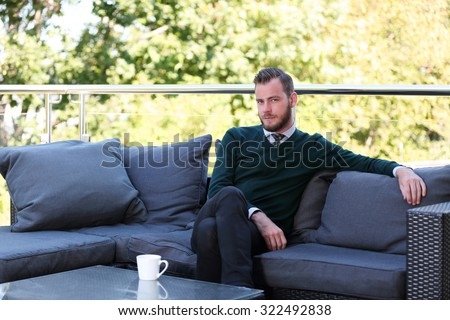 A handsome man in a shirt, tie and sweater sitting down outside on a summer day holding a mug. Relaxed and laid back. - stock photo