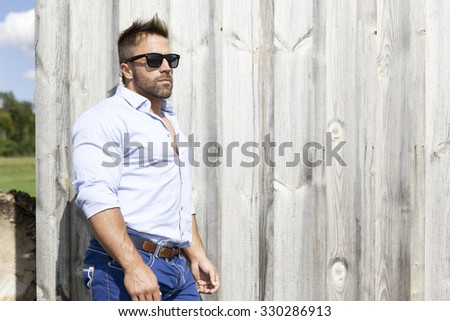 A handsome man outdoor in front of a wooden background wall