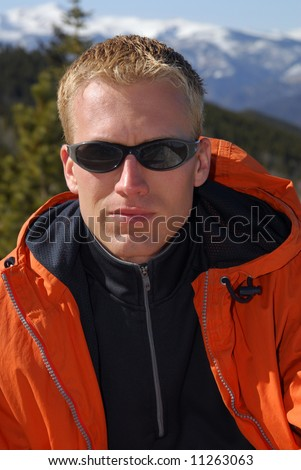 A handsome man outside in the Rocky Mountains - stock photo