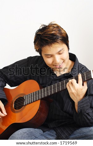 A handsome man playing guitar