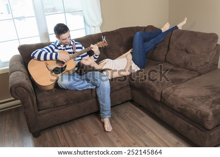 A Handsome man serenading his girlfriend with guitar at home in the living room - stock photo