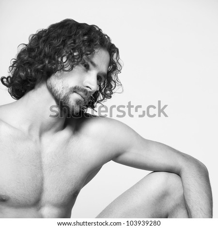 a handsome man sitting bare-chested poses in the studio - stock photo