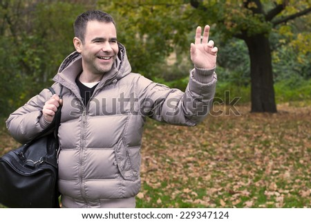 a handsome man standing in a park and greeting someone