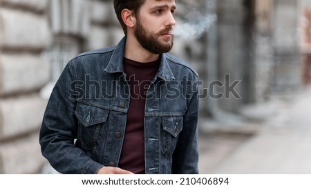 A handsome man with a beard in a jeans jacket on the street smoking - stock photo
