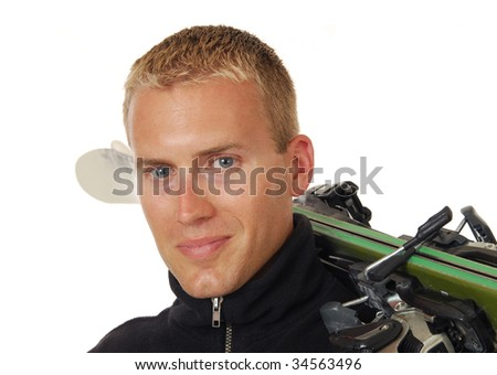 A handsome man with a set of skis over his shoulder - stock photo