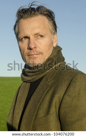 A handsome mature man with beard wearing a green scarf and jacket. - stock photo