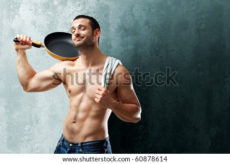 A handsome muscular cook posing with a pan on his shoulder on a textrured backgound with space for text