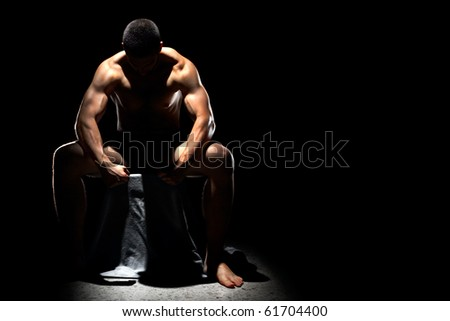 A handsome muscular man posing on a black background sitting down and resting with his head bowed - stock photo