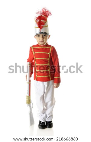 A handsome, preschool Christmas soldier standing straight and tall while supporting his gun.  On a white background. - stock photo