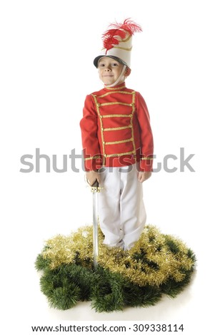 A handsome preschool Christmas soldier standing straight and tall with his sword down by his side.  He's surrounded by green and gold garland.  On a white background. - stock photo