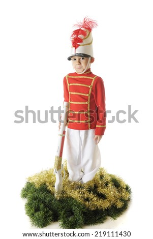 A handsome preschooler standing erect in his Christmas soldier uniform.  He's supports his rifle and is surrounded by green and gold garland.  On a white background. - stock photo