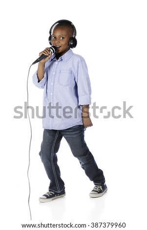 A handsome preteen boy wearing earphones as he makes his announcement over a mike.  On a white background. - stock photo
