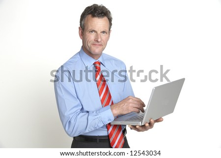 A handsome senior businessman smiles to the camera whilst working on his laptop