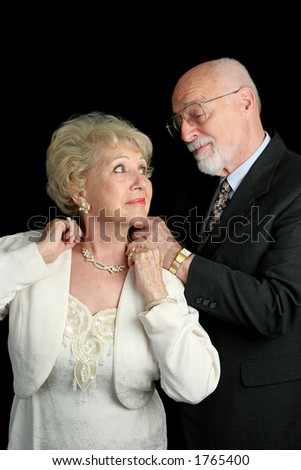 A handsome senior couple getting ready for a special occasion.  He is fastening her necklace for her. - stock photo