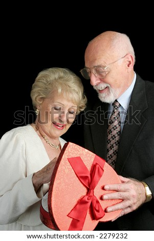 A handsome senior man giving a box of Valentine chocolate to his beautiful wife.  Black background. - stock photo