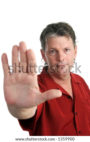 A handsome, serious man holding his hand out in a stop gesture.  Focus on man's face. Isolated. - stock photo