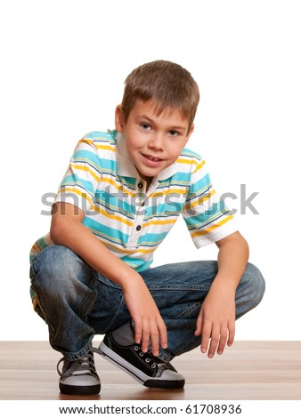A handsome smiling kid in casual clothes squats; isolated on white
