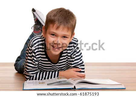 A handsome smiling kid is reading a thick book