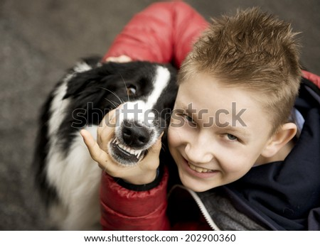 a handsome smiling teenager boy with his dog  - stock photo
