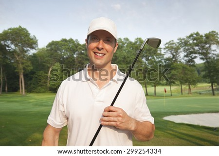 A handsome,smiling, young male golfer holds a club on a golf course - stock photo