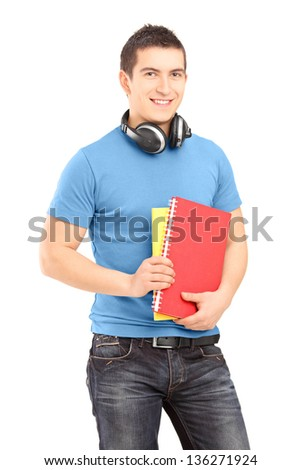A handsome student with headphones holding books isolated on white background