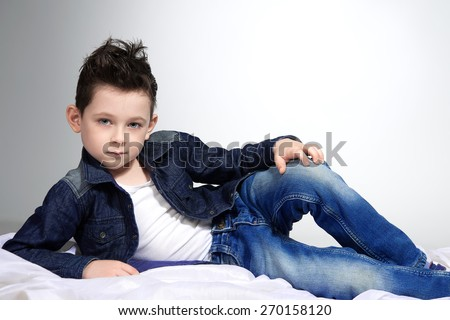 A handsome stylish guy is lying on the white sheet. He is wearing a white t-shirt and denim suit - stock photo