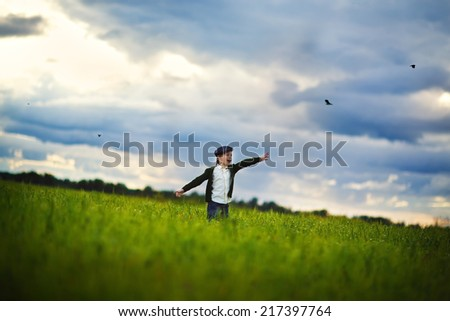 A handsome stylish little boy running in the meadow and trying to fly as a bird in a warm summer evening against the beautiful sky with clouds.