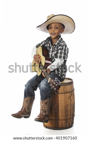 A handsome young African boy happily singing and playing his guitar as he sits on an old barrel.  On a white background. - stock photo