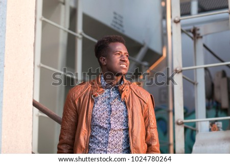 A handsome young black man in sunlight in an industrial setting