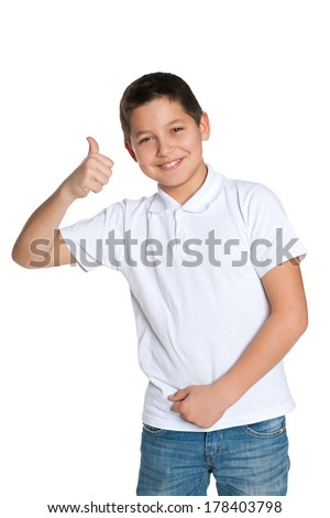 A handsome young boy in the white shirt holds his thumb up - stock photo