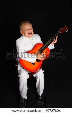 A Handsome Young Boy singing, in a White Suit and with Guitar - stock photo