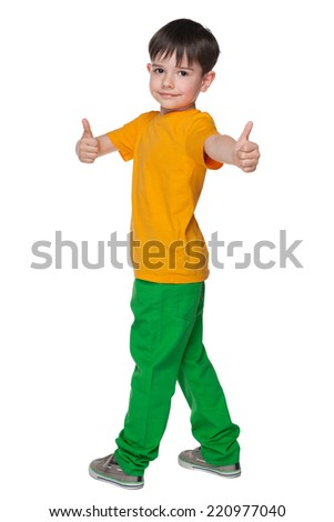 A handsome young boy with his thumbs up looks back - stock photo