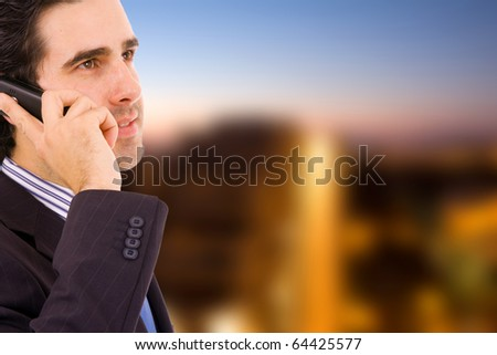 A handsome young business man at a modern office building on the phone - stock photo