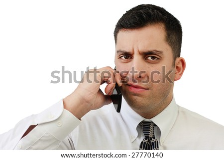 A handsome young businessman confused while talking on a cell phone over white - stock photo