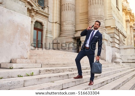 A handsome young businessman walking down on the stairs while talking on his phone