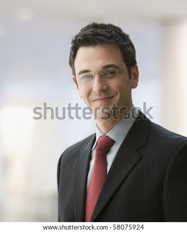 A handsome young businessman wearing glasses and smiling. Vertical shot. - stock photo