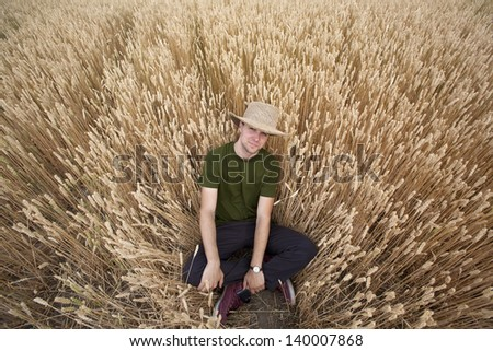 A handsome young country boy with straw hat on sitting in a golden wheat field. - stock photo