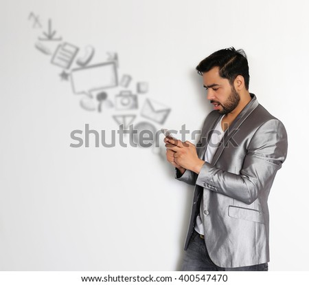 A handsome young Indian man checking email, chatting, internet browsing, on Mobile against a white background - stock photo